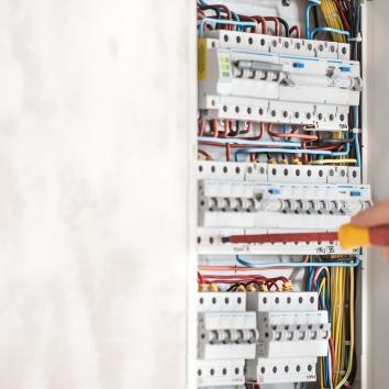 electrical-technician-working-switchboard-with-fuses-985b54ba012e09e5df3fb10766cbcba5.jpg